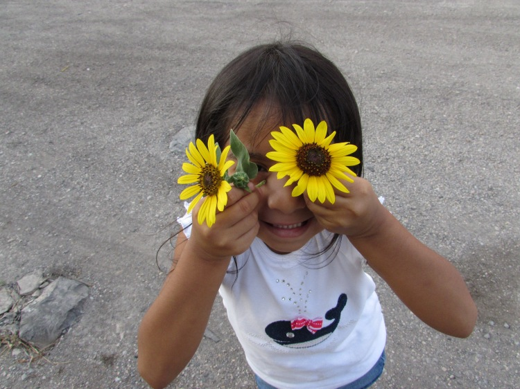 My silly niece with some small flowers we picked alongside of the restaurant.