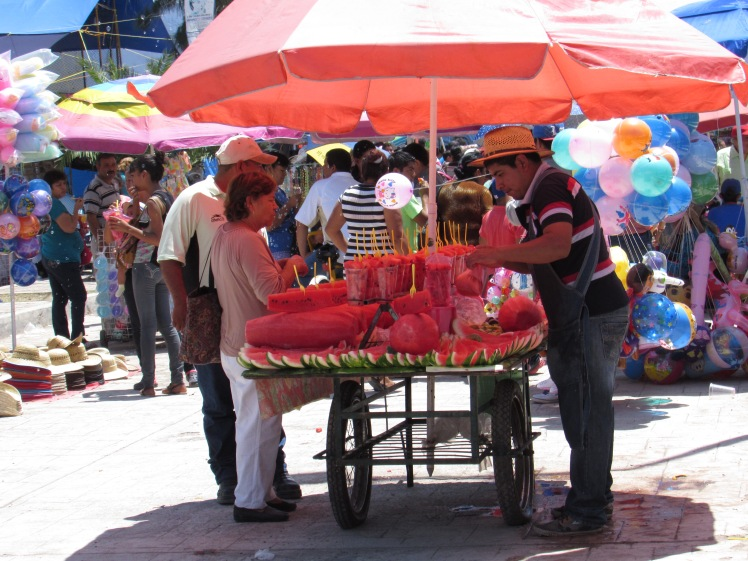 Vendor selling watermelon in a cup.