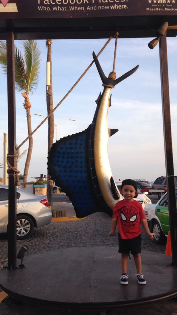 My nephew posing in front of a marlin.